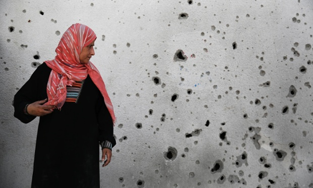 A Palestinian woman looks at a shrapnel-scarred wall at the hospital in Beit Hanoun town.