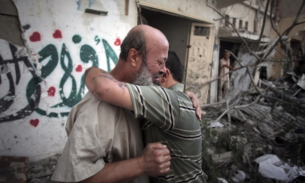 Palestinians hug each other after seeing their homes destroyed, during a 12-hour cease-fire in Gaza City's Shijaiyah neighborhood.