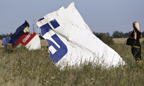 A woman takes a photograph of wreckage at the crash site of Malaysia Airlines flight MH17. Photograph: Sergei Karpukhin/Reuters