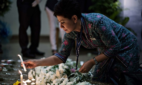 A Malaysia Airlines flight attendant in Kuala Lumpur lights a candle during a special multi-faith prayer for the MH17 crash victims. Photograph: Mohd Rasfan/AFP/Getty