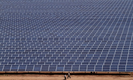Indian workers walk past solar panels at the 200 megawatts Gujarat Solar Park at Charanka in Patan district, India, Saturday, April 14, 2012.