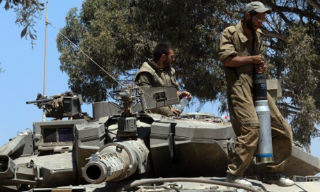 An Israeli soldier carries a tank shell onto a Merkava tank inside southern Israel, close to the Gaza Strip, 31 July 2014.