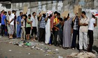 Palestinians wait in line to buy bread outside a bakery in Gaza City