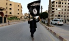 A militant waves a black Isis flag in Iraq