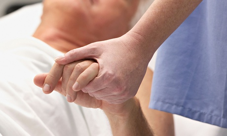 Doctor holding male patient  s hand in hospital room