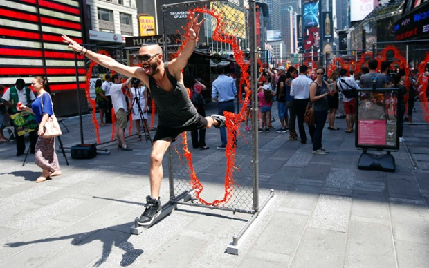 A man leaps through one of a series of 17 sculptures consisting of copper and steel panels cut out with human silhouettes of various sizes by Cuban-born artist Arles del Rio in New York's Times Square
