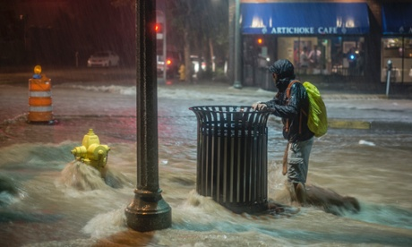 A man hangs on to a trash can as rainwater gushes towards Albuquerque in New Mexico, US. Heavy rains caused flash flooding and road closures in the city earlier this month. Photograph: Roberto E. Rosales/AP