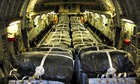 A US air force transport plane is loaded with bottles of water