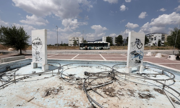 Tthe remains of a fountain decorated with the Olympic rings and graffiti-defaced marble blocks dedicated to Greek Olympic medal winners are seen at the Olympic village.