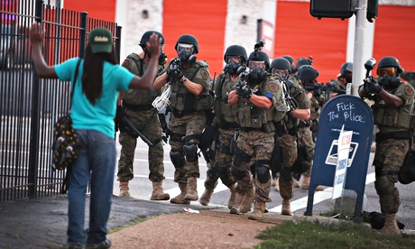 Armed police confront a protester in Ferguson, Missouri