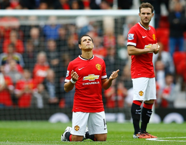 Javier Hernandez, in the starting line-up, prays on the pitch before the match.