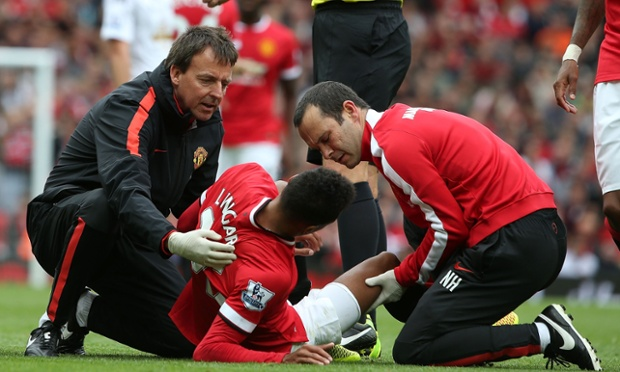 Jesse Lingard receives treatment after a crunching tackle from Ashley Williams.
