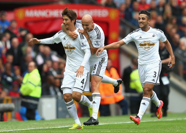 He celebrates scoring with team-mates Jonjo Shelvey and Neil Taylor.