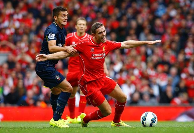 Liverpool's Jordan Henderson (R) is challenged by Southampton's Dusan Tadic.