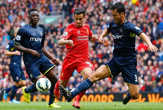 Liverpool's Philippe Coutinho (C) is challenged by Southampton's Maya Yoshida.