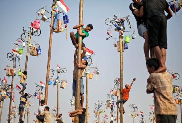 Participants struggle to reach the prizes during a greased-pole climbing competition held as a part of the independence day celebrations in Jakarta, Indonesia.