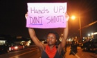 Protesters hold signs during a protest on West Florissant Road in Ferguson, Missouri.