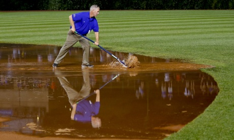 A member of the grounds crew works on the field after a heavy rain soaked Wrigley Field during the fifth inning of a baseball game between the San Francisco Giants and the Chicago Cubs on Tuesday.