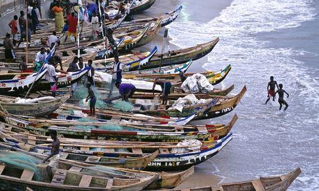 Ghana fishermen with long boats on shore