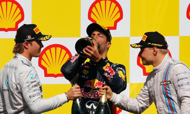 Red Bull's winning driver Daniel Ricciardo drinks what is left as Nico Rosberg from Mercedes, left, and Williams driver Valtteri Bottas celebrate by touching bottles.