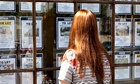 A young woman looks into the window of an estate agent