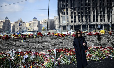 A woman stands near a makeshift memorial in Kiev's Independence Square in February 2014