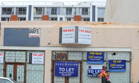 All over Woodstock there are premises for sale or to rent, with many once housing local businesses unable to afford the increased rents. In the background is one of the new, upmarket blocks of flats that have sprung up to accommodate people moving into the area, a sign of the growing gentrification taking place. For Cities: gentrification of Woodstock. Cape Town, South Africa