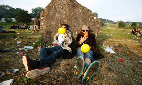 People inhaling laughing gas at the Glastonbury festival.