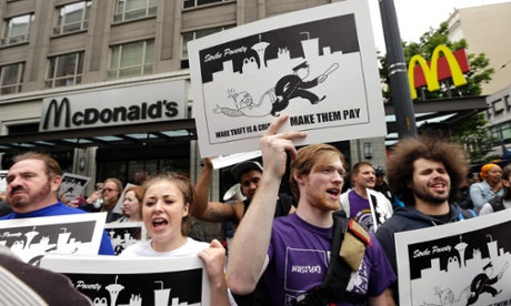 Demonstrators protesting what they say are low wages and improper treatment for fast-food workers stand near a McDonald's in Seattle.