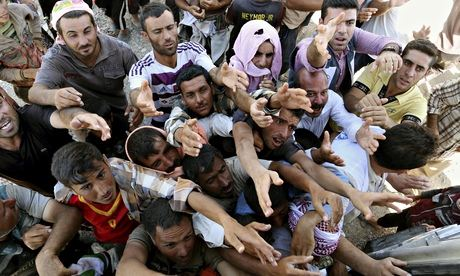 Displaced Iraqis from the Yazidi community gather for humanitarian aid