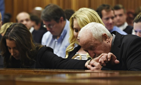 Henke Pistorius kisses the hand of his daughter Aimee during the verdict hearing of his son Oscar