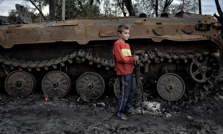 Nikita, 10, plays with a burned rifle at a site where a Ukrainian military convoy was destroyed. Photograph: Maria Turchenkova