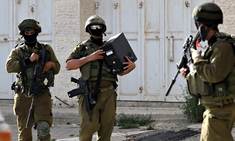 An Israeli soldier carries a computer seized in Hebron during search for three Israeli teenagers