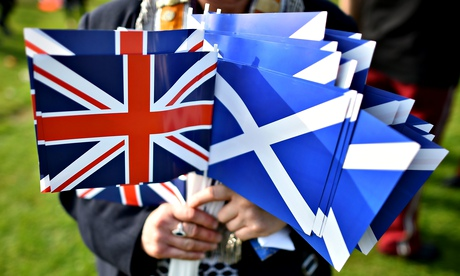 A no vote supporter holds Union Jack and Scotland flags