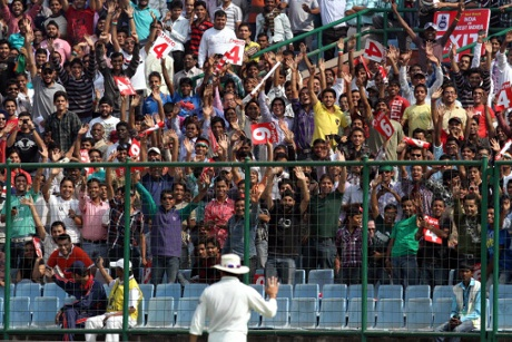 Members of the crowd cheer as Sachin Tendulkar approaches the boundary rope during Ferozshah Kotla cricket stadium