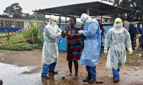 Liberian nurses in protection suits escort a suspected Ebola patient in Monrovia