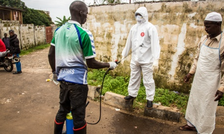 A health worker in a protective suit is sprayed with disinfectant by a colleague in Freetown, Sierra Leone