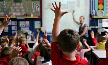 Schoolchildren raise their hands to answer a question from the teacher.