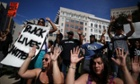 Demonstrators hold their hands up during a moment of silence 14 August in Oakland, California.