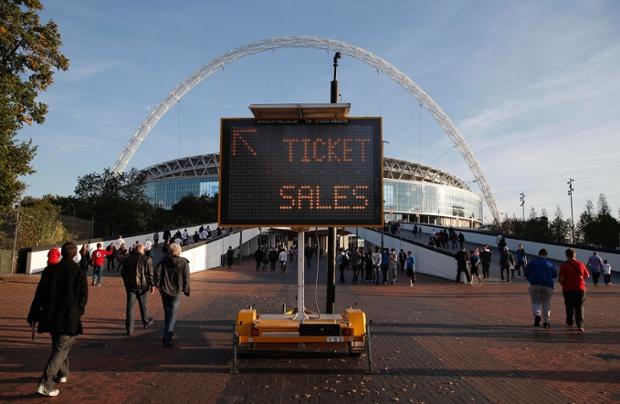 Spectators arrive past a sign advertising ticket sales.