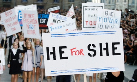 A model holds a sign reading 'He for She' on the Chanel catwalk.