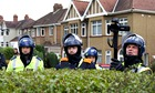 Police personnel stand behind a hedge