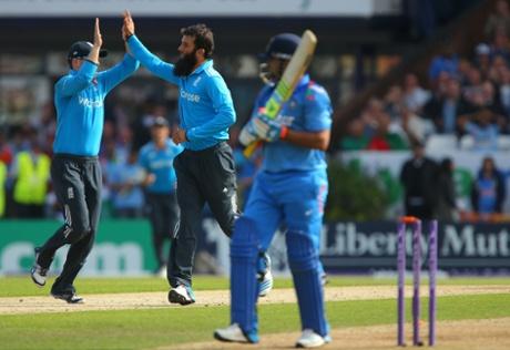 England s Moeen Ali celebrates taking the wicket of India s Suresh Raina.