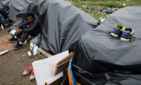 An Eritrean migrant sits outside his makeshift shelter close to a chemical factory in Calais