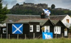 A Yes Scotland supporter finishes decorating his home in the shadow of Stirling Castle in the run up to the vote.