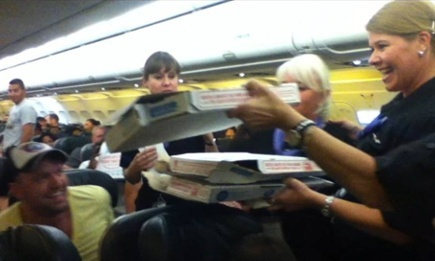 Air stewards hand pizza to passengers stuck on the stranded plane