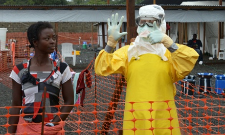 A medical worker gestures beside a woman inside a high-risk area where Ebola patients are being treated in Monrovia, Liberia.