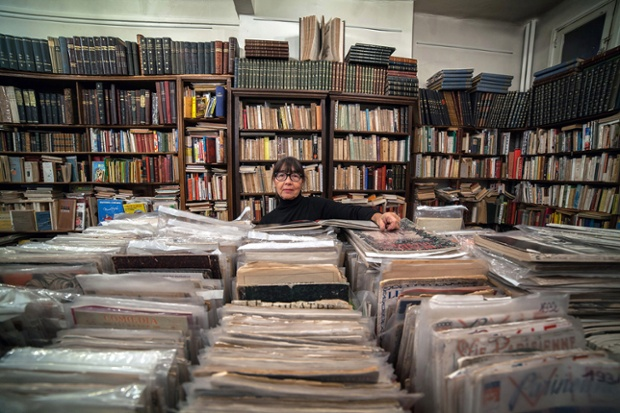 Edwige is dwarfed by stacks of vintage magazines in Paris, France.