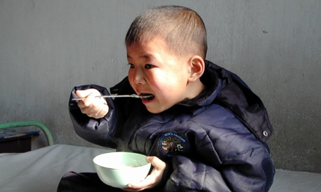 A boy eats enriched food supplied by the United Nations World Food Programme (WFP) at a hospital in south Pyongan province in 2004.
