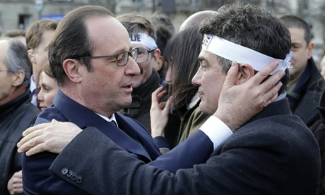Hollande comforts Charlie Hebdo columnist Patrick Pelloux at the solidarity march.